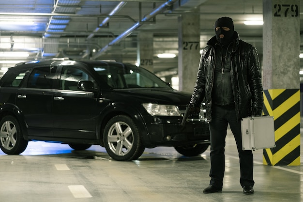 Gangster in black jacket and balaclava holding handgun and suitcase while standing on background of car in parking area