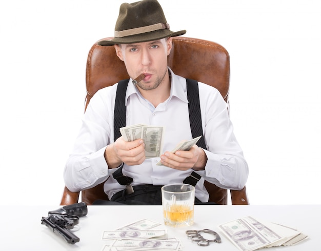 Gangster sitting at a table counting money.