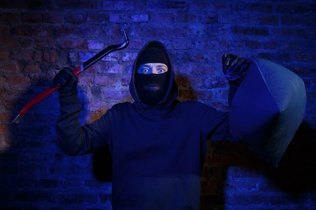 벽돌 벽 근처에 마스터 키와 가방이 있는 갱스터