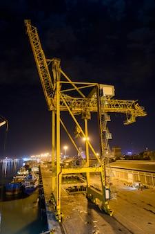 Козловой кран в порту в ночное время. желтый журавль и темное небо.
