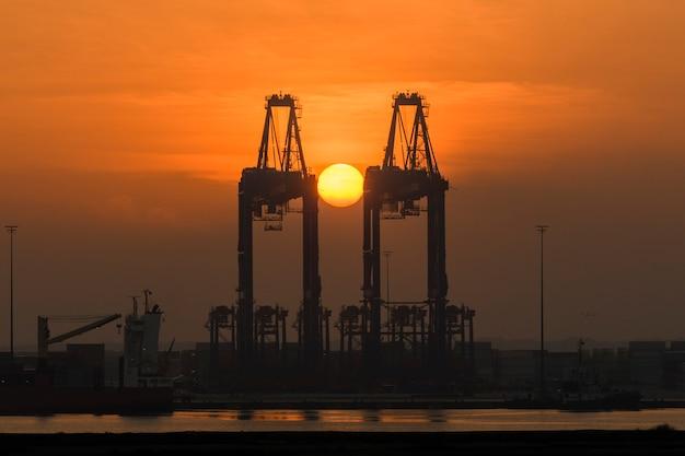 Козловой кран с восходом солнца. утро в порту.