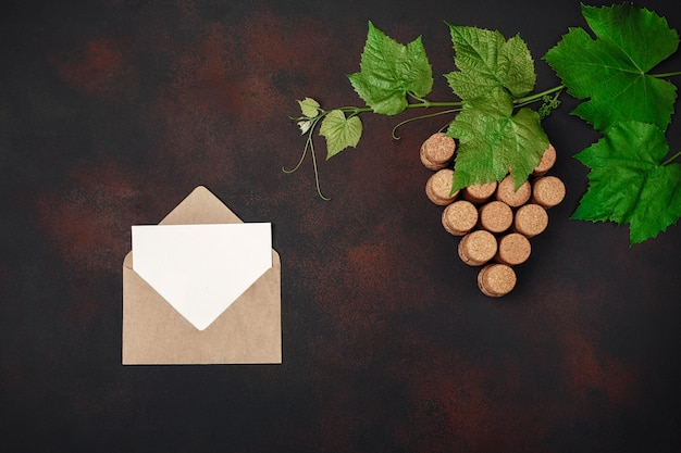 Gape bunch of cork with leaves, envelope and letter on rusty background.