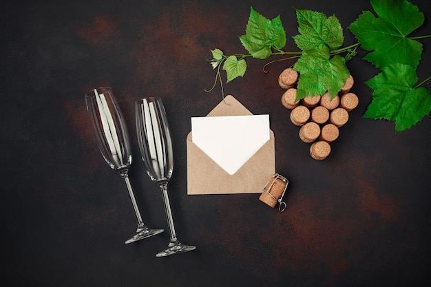 Gape bunch of cork with leaves, two wineglass, envelope and letter on rusty background.
