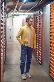 Подвал гаража молодой взрослый человек в куртке и джинсах стоит, держа руку в кармане в освещенном подвале