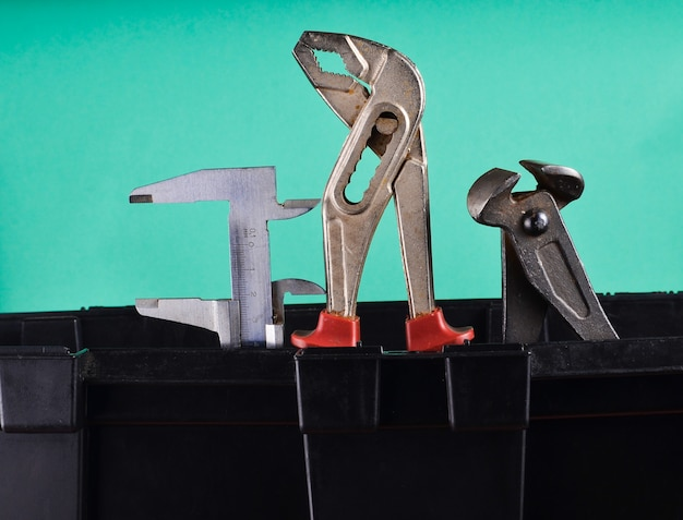 Гараж пластиковый ящик для инструментов с рабочими инструментами, изолированных на синем. щипцы, гаечный ключ, суппорт