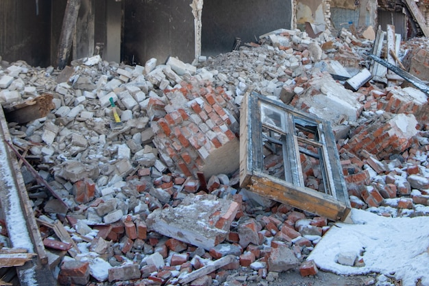 Мусор и мусор, кирпичи, фрагменты деревянных стен, старое окно после катаклизма, землетрясения.