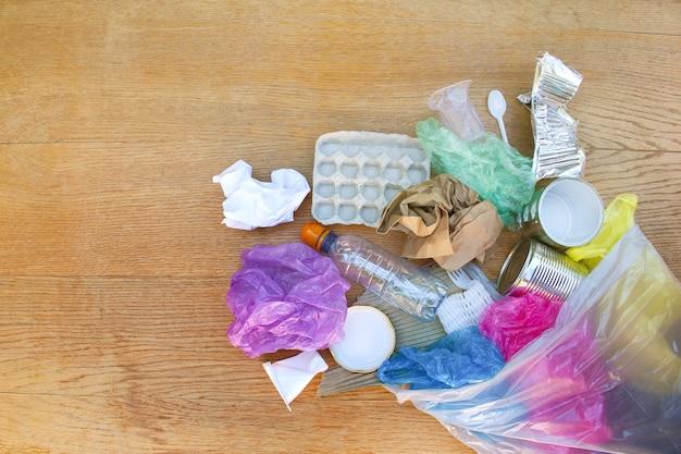 木製の背景にさまざまなゴミとゴミ袋。フラットレイ。