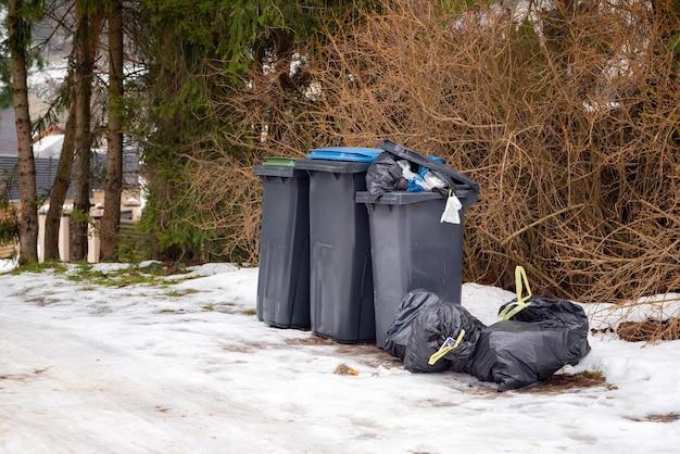 겨울에 주거 지역의 하얀 눈 위에 쓰레기로 가득 찬 쓰레기통.