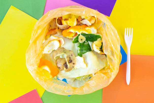 ゴミ、色付きの抽象的な背景のビニール袋に食品廃棄物。地球の生態と汚染。ごみの分別。