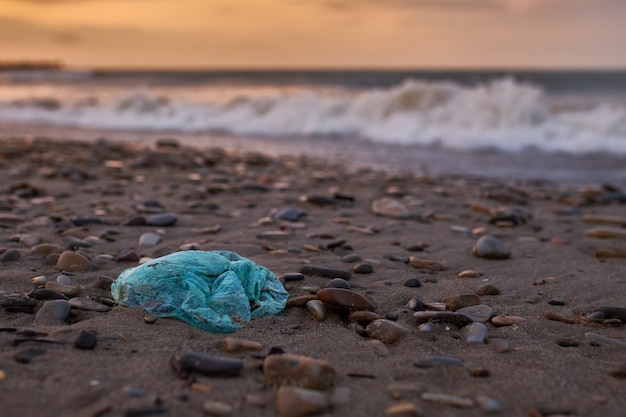 Garbage in the form of a plastic bag lying on the beach