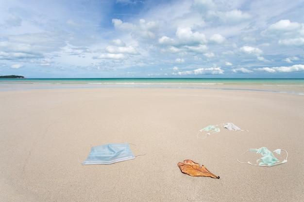 Мусор от использованных медицинских масок на пляже.