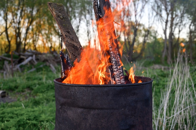 さびた金属バレルでのごみ焼却。樽の土地区画からの燃える枝と古い草。