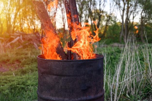 さびた金属バレルでのごみ焼却。