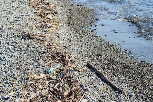 ゴミ、がらくた、ごみ、小石の海岸の海のビーチで壊れた木の枝、環境保護の概念、水平ライフスタイルストックフォト画像写真の背景