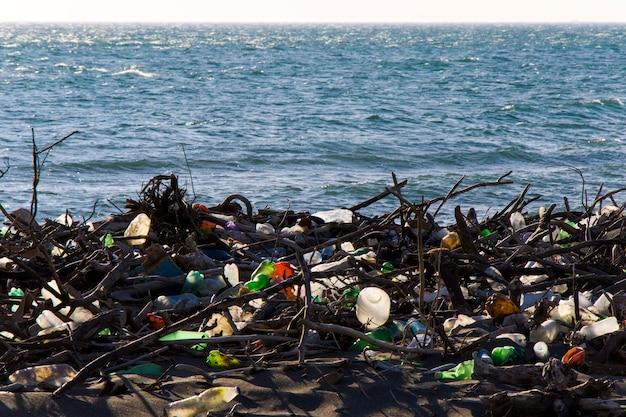 Мусор на песчаном пляже, загрязнение пластиком и металлами, глобальное потепление и загрязнение воды