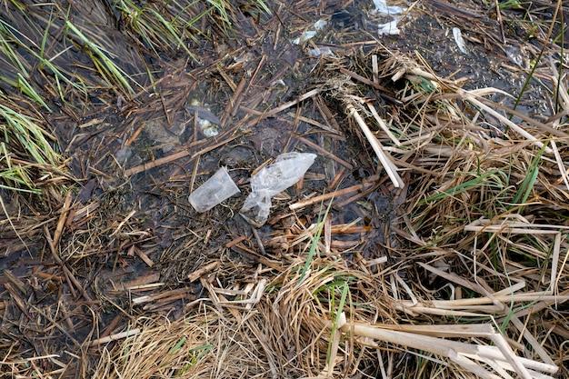 Мусор на берегу озера. пластиковые пакеты и бутылки загрязняют окружающую среду. концепция защиты и сохранения окружающей природы. фото высокого качества