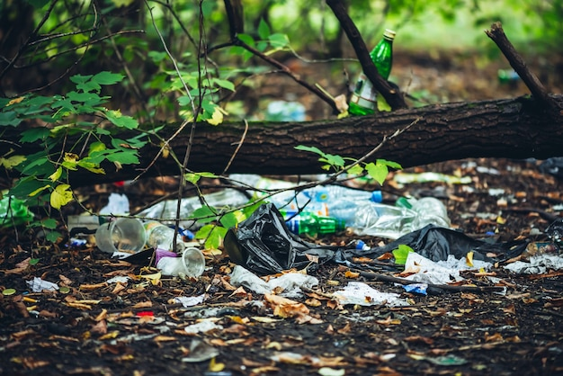 Garbage pile in forest among plants. toxic plastic into nature everywhere.