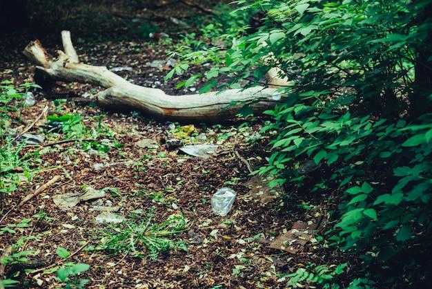 Куча мусора в лесу среди растений. токсичный пластик проникает в природу повсюду. мусорная куча в парке среди растительности. загрязненная почва. загрязнение окружающей среды. экологическая проблема. выбрасывайте мусор куда угодно.