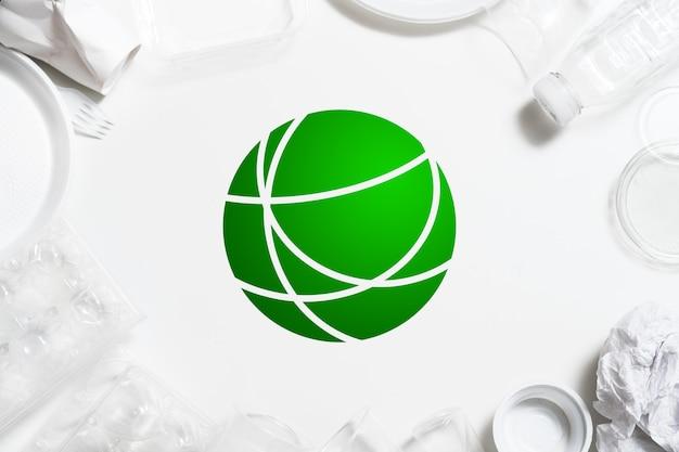 Переработка мусора. защита окружающей среды. пластиковая посуда, расположенная вокруг зеленого символа.