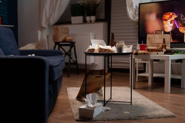 空のビールの飲み物のボトルと食べ物のゴミがリビングルームに置かれたゴミテーブル