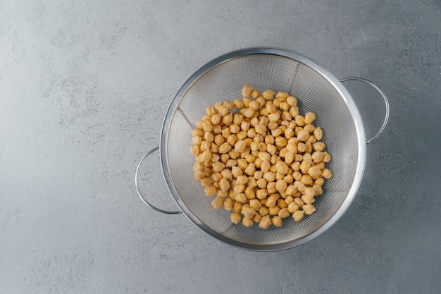Взгляд сверху сухих свежих нутов или garbanzo в сетке.