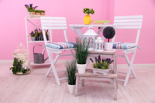 Garden chairs and table with flowers on shelves on pink