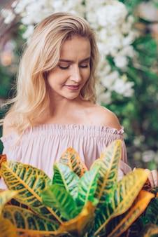 屋外の庭で金髪の若い女性の前で庭のクロトン