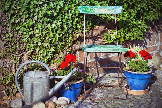Садовый декор - стул, цветы в горшках и лейка