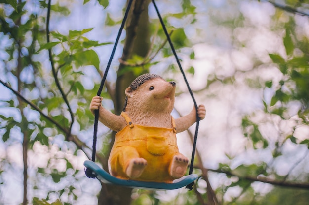 Garden figurine decor - a cheerful hedgehog in yellow clothes sitting on a swing