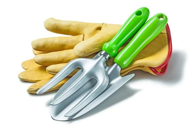 Garden fork and hand spade on gloves isolated