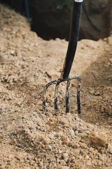夏の別荘で乾燥した粘土質の土壌に突き刺さった庭のフォーク