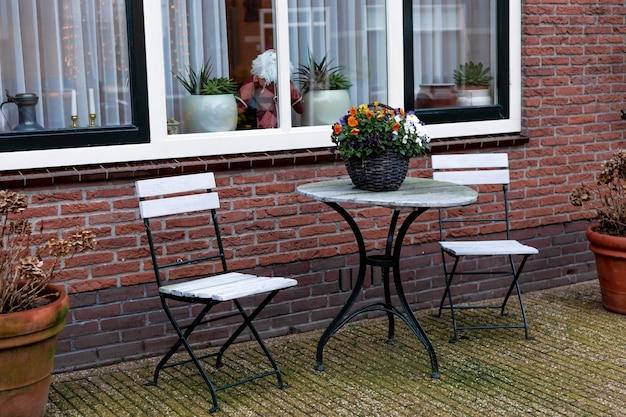 야외 식물이 있는 집 현관에 있는 정원 가구. 조경 도시에서 정원 가꾸기. 커피 테이블에 냄비에 피는 꽃. 네덜란드의 가을이나 겨울에 쉴 수 있는 곳. 집 야외 식물.