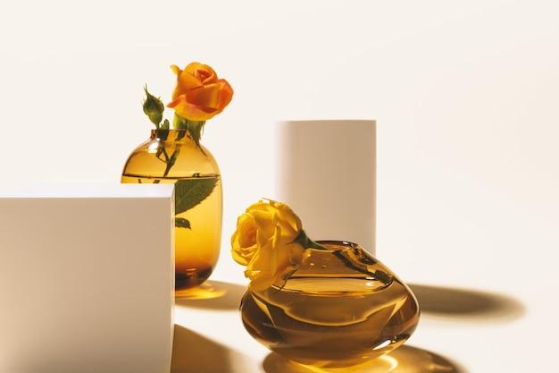 ガラスの花瓶の庭の小さなバラとハード長い影とベージュの背景に白い表彰台