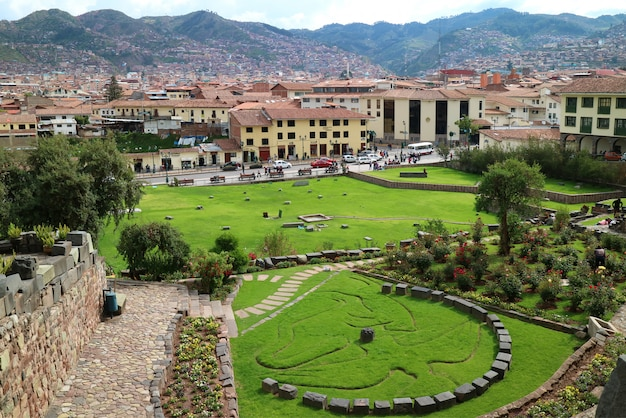 Garden outside coricancha temple in cusco of peru, with the symbol of inca mythology of condor