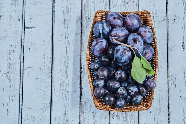 Prugne da giardino in un cesto su sfondo blu. foto di alta qualità