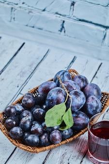Prugne da giardino in un cesto su sfondo blu con un bicchiere di succo. foto di alta qualità