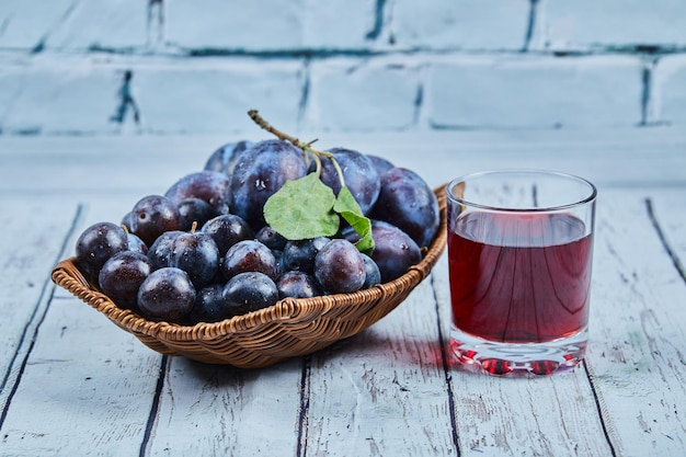 Garden plums in a basket on a blue background with a glass of juice. high quality photo