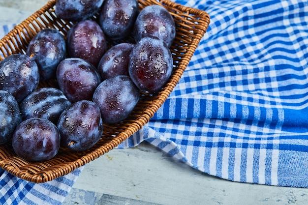 Prugne da giardino in un cesto su un tavolo di pietra con tovaglia. foto di alta qualità
