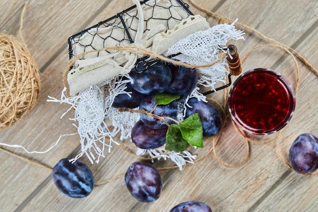 Prugne da giardino in un cesto su un tavolo di legno con un bicchiere di succo. foto di alta qualità