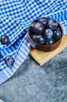 Garden plums in a bowl on marble with tablecloth.