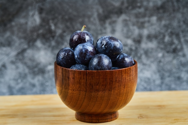 Garden plums in a bowl on wooden table.