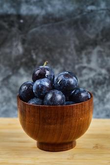 Prugne da giardino sulla ciotola sul tavolo di legno.