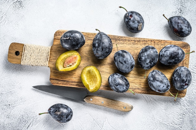 Garden plums on a  cutting board. gray background. top view.