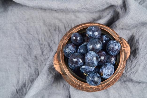 灰色のテーブルクロスのボウルに庭の梅。高品質の写真