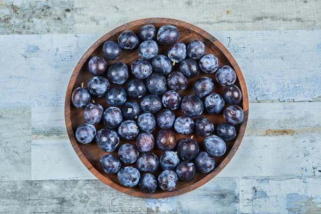 Prugne da giardino in un piatto su sfondo blu. foto di alta qualità