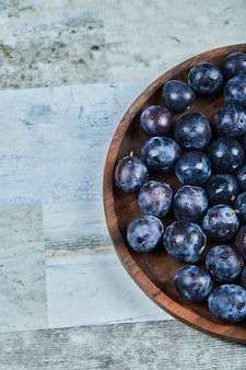 Prugne da giardino in un piatto sull'azzurro.
