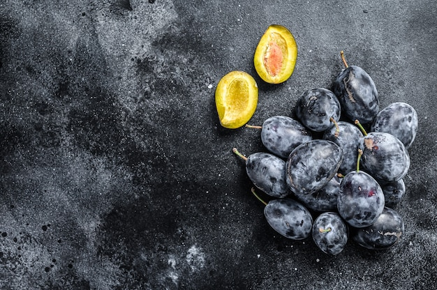 Garden plums on stone table. black background. top view. copy space.