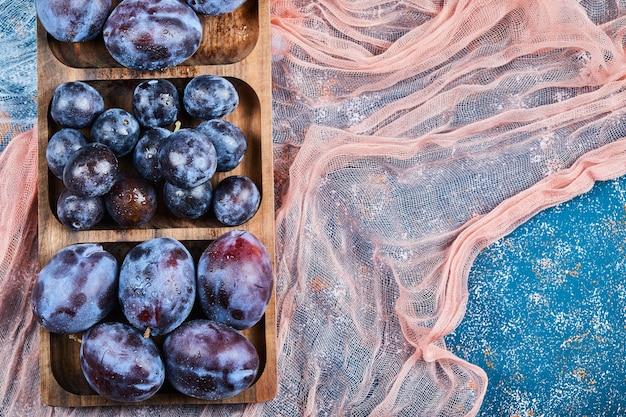 Prugne da giardino sul piatto di legno e sul blu con tovaglie.
