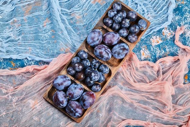 Prugne da giardino su piatto di legno e su blu con tovaglie.