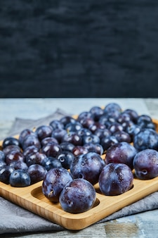 Garden plums on wooden platter and on dark background. high quality photo